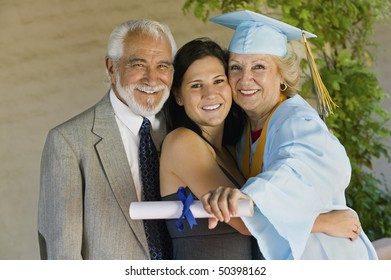 Senior graduate hugging granddaughter with husband outside