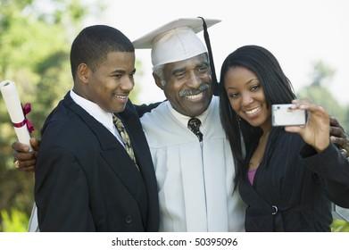 Senior graduate taking picture with grandchildren outside