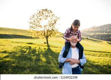 A senior grandfather giving a small granddaughter a piggyback ride in nature.