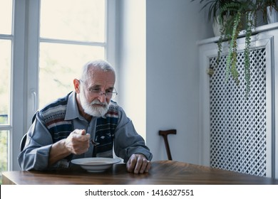 Senior grandfather with grey hair and beard sitting alone in the kitchen eating breakfast