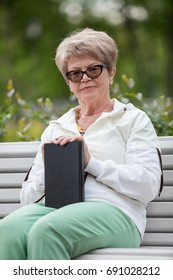 Senior grandmother with black book in hands sitting on the bench in park, looking at camera