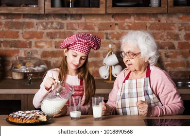 Senior grandmother with granddaughter drinking milk at kitchen
