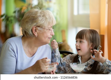 Senior grandmother with granddaughter eating tasty ice cream together