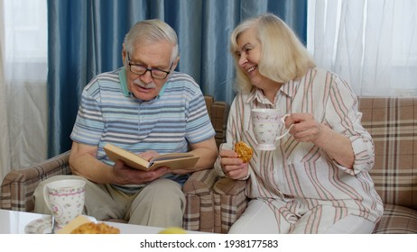 Senior grandmother, grandfather enjoying coffee having conversation relaxing sit on sofa at home. Retired old mature couple talking drinking tea, reading book in modern living room lounge together.