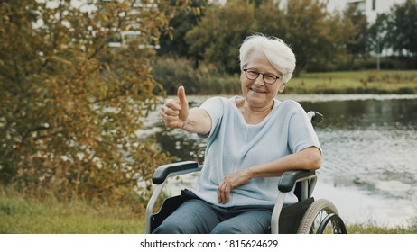 Senior gray haired lady in the wheelchair neear the river showing thumbs up. High quality photo