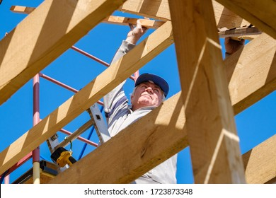 Senior gray-haired builder collects the frame of a wooden country house standing on the stairs against the blue sky. The physical activity of the elderly. Eco-friendly housing made of wood.