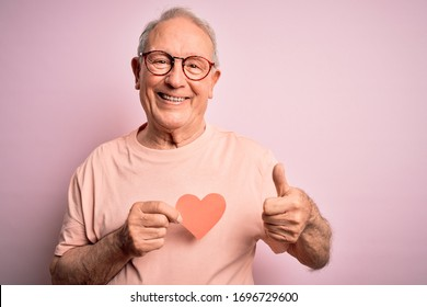 Senior grey haired man holding heart shape paper over pink background happy with big smile doing ok sign, thumb up with fingers, excellent sign