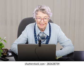 Senior grey haired teacher looking at laptop screen. She is teaching on-line English (or any) language. Teacher is wearing blue blouse and dark blue stone necklace with pendant.