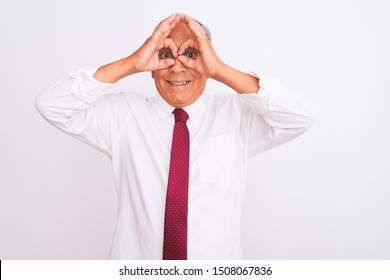Senior grey-haired businessman wearing elegant tie over isolated white background doing ok gesture like binoculars sticking tongue out, eyes looking through fingers. Crazy expression.
