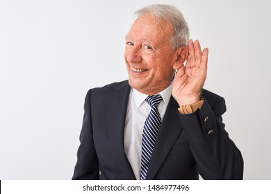 Senior grey-haired businessman wearing suit standing over isolated white background smiling with hand over ear listening an hearing to rumor or gossip. Deafness concept.