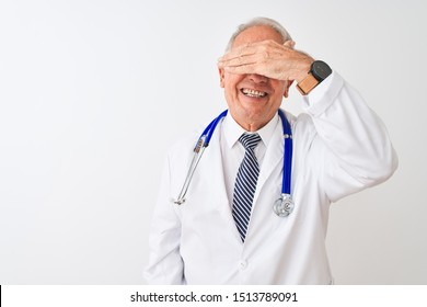 Senior grey-haired doctor man wearing stethoscope standing over isolated white background smiling and laughing with hand on face covering eyes for surprise. Blind concept.