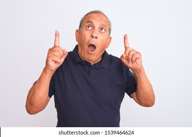 Senior grey-haired man wearing black casual polo standing over isolated white background amazed and surprised looking up and pointing with fingers and raised arms.