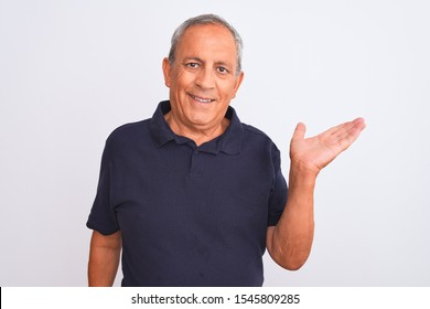 Senior grey-haired man wearing black casual polo standing over isolated white background smiling cheerful presenting and pointing with palm of hand looking at the camera.