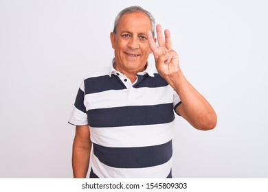 Senior grey-haired man wearing casual striped polo standing over isolated white background showing and pointing up with fingers number three while smiling confident and happy.