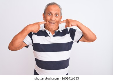 Senior grey-haired man wearing casual striped polo standing over isolated white background smiling cheerful showing and pointing with fingers teeth and mouth. Dental health concept.