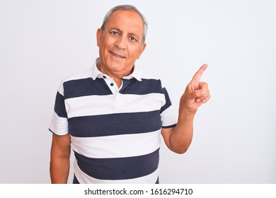 Senior grey-haired man wearing casual striped polo standing over isolated white background with a big smile on face, pointing with hand and finger to the side looking at the camera.