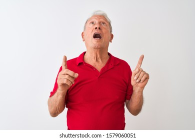 Senior grey-haired man wearing red polo standing over isolated white background amazed and surprised looking up and pointing with fingers and raised arms.
