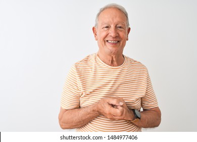 Senior grey-haired man wearing striped t-shirt standing over isolated white background with hands together and crossed fingers smiling relaxed and cheerful. Success and optimistic