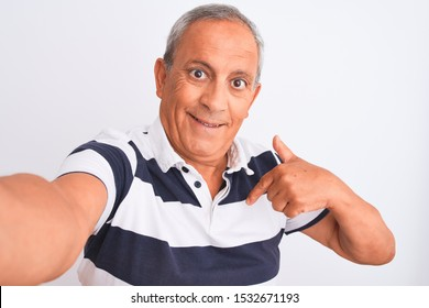 Senior grey-haired man wearing striped polo make selfie over isolated white background with surprise face pointing finger to himself