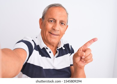 Senior grey-haired man wearing striped polo make selfie over isolated white background very happy pointing with hand and finger to the side