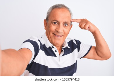 Senior grey-haired man wearing striped polo make selfie over isolated white background very happy pointing with hand and finger