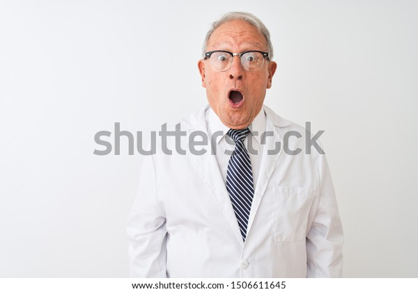 Senior grey-haired scientist man wearing coat standing over isolated white background afraid and shocked with surprise expression, fear and excited face.