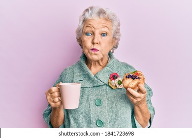 Senior grey-haired woman drinking a cup of coffee and eating bun puffing cheeks with funny face. mouth inflated with air, catching air.