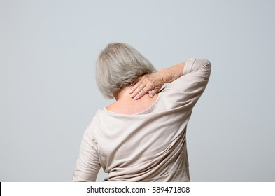 Senior grey-haired woman from her back touching neck, as if suffering from chondrosis pain, standing over plain grey background