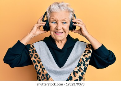 Senior grey-haired woman listening to music using headphones smiling with a happy and cool smile on face. showing teeth.