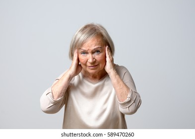 Senior grey-haired woman touching her temples with her both hands to her head, sadly looking at camera as if suffering from headache, standing against plain grey background