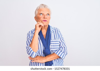 Senior grey-haired woman wearing blue striped shirt standing over isolated white background with hand on chin thinking about question, pensive expression. Smiling with thoughtful face. Doubt concept.