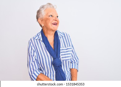Senior grey-haired woman wearing blue striped shirt standing over isolated white background looking away to side with smile on face, natural expression. Laughing confident.