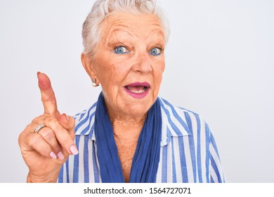 Senior grey-haired woman wearing blue striped shirt standing over isolated white background surprised with an idea or question pointing finger with happy face, number one