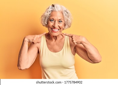 Senior grey-haired woman wearing casual clothes smiling cheerful showing and pointing with fingers teeth and mouth. dental health concept.