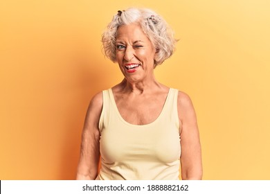 Senior grey-haired woman wearing casual clothes winking looking at the camera with sexy expression, cheerful and happy face.