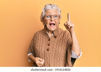 Senior grey-haired woman wearing casual clothes and glasses pointing finger up with successful idea. exited and happy. number one.