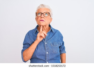 Senior grey-haired woman wearing denim shirt and glasses over isolated white background Thinking concentrated about doubt with finger on chin and looking up wondering