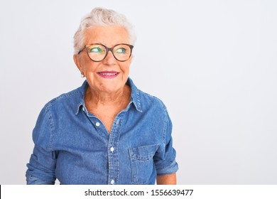 Senior grey-haired woman wearing denim shirt and glasses over isolated white background smiling looking to the side and staring away thinking.