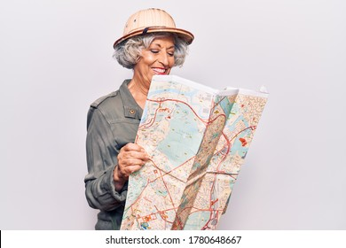 Senior grey-haired woman wearing explorer hat holding map looking positive and happy standing and smiling with a confident smile showing teeth