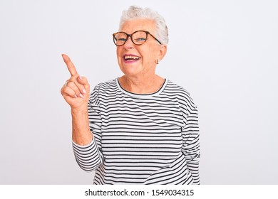 Senior grey-haired woman wearing striped navy t-shirt glasses over isolated white background with a big smile on face, pointing with hand and finger to the side looking at the camera.