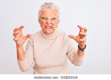 Senior grey-haired woman wearing turtleneck sweater standing over isolated white background Shouting frustrated with rage, hands trying to strangle, yelling mad