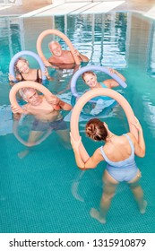 Senior group in aqua fitness with swimming noodle