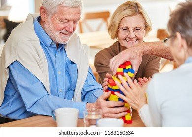Senior group with dementia stacks together colorful building blocks in retirement home