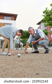 Senior group playing boule together outside in a city