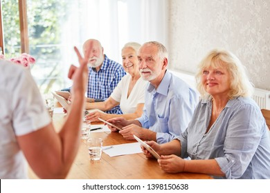 Senior group in retirement home while learning together in computer class