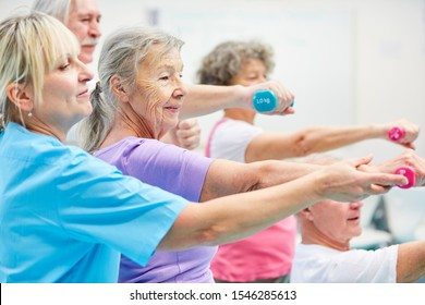 Senior group trains with dumbbells for health and strength in rehab