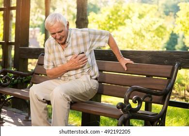 Senior guy has heartache. Elderly man on park bench. Too much stress. Chronic disease of heart.