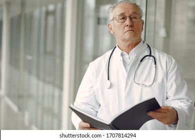 Senior in a hall. Doctor in a uniform. Man in a glasses.