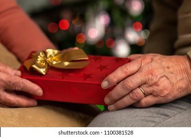 Senior hands exchange christmas present - closeup