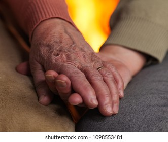 Senior hands holding each other with fireplace in background - growing old together concept